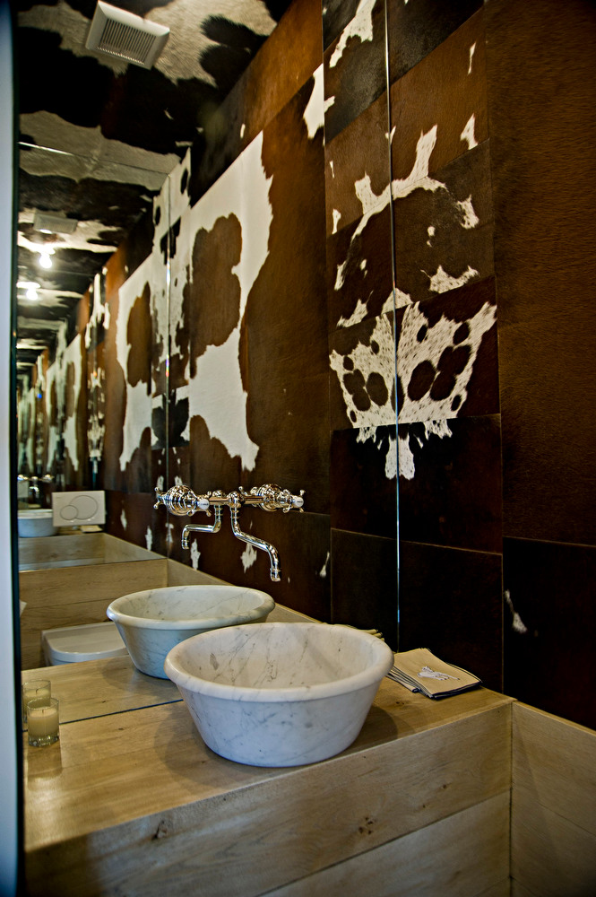 Powder room with cowhide walls, ceiling and mirror